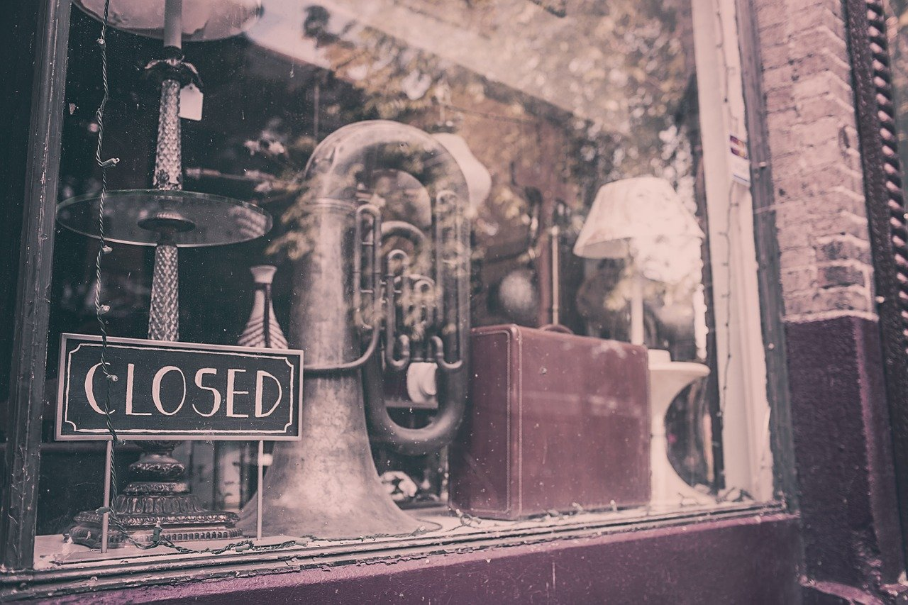 shop window with a closed sign, showing a tuba and other items