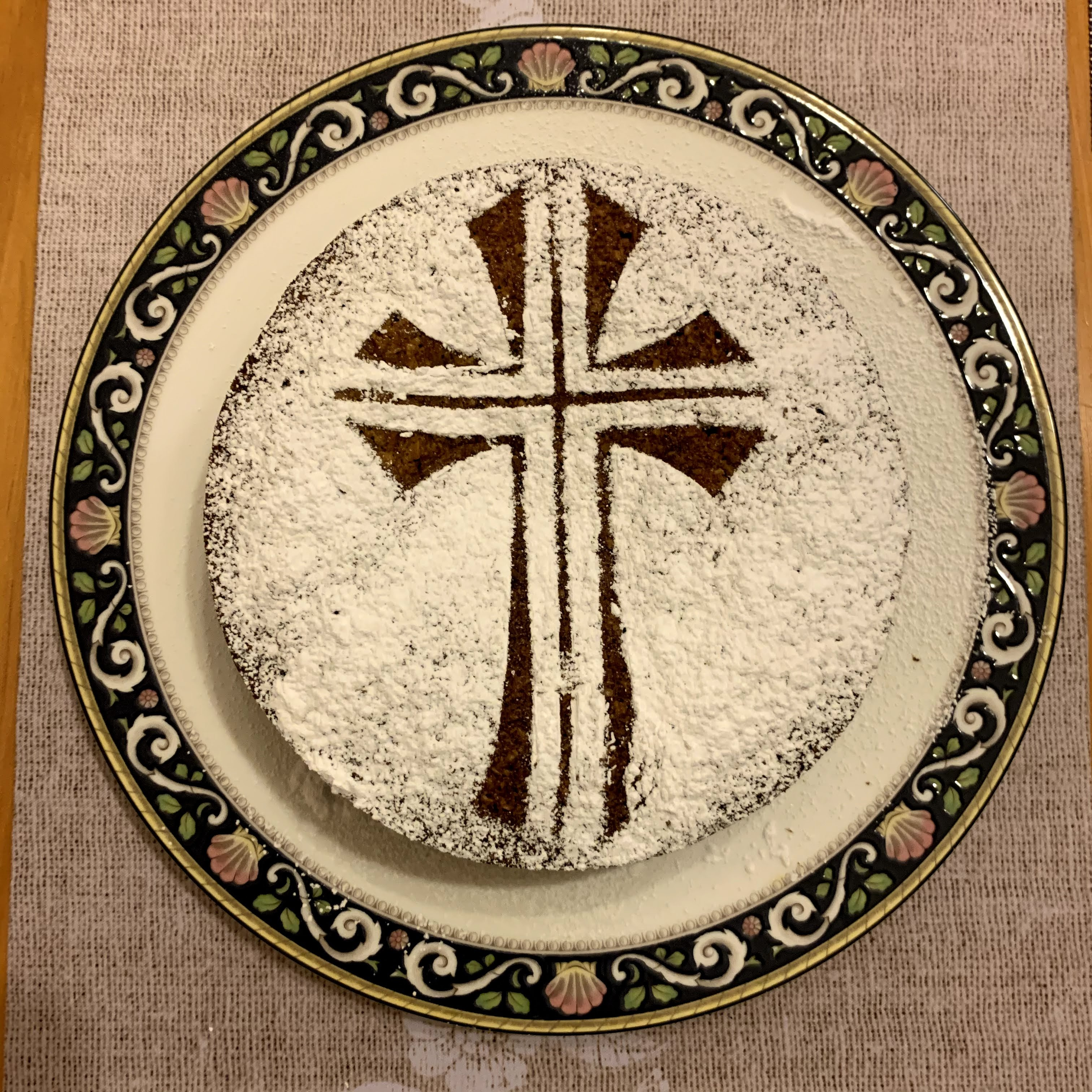 carrot cake with icing sugar in the shape of a cross