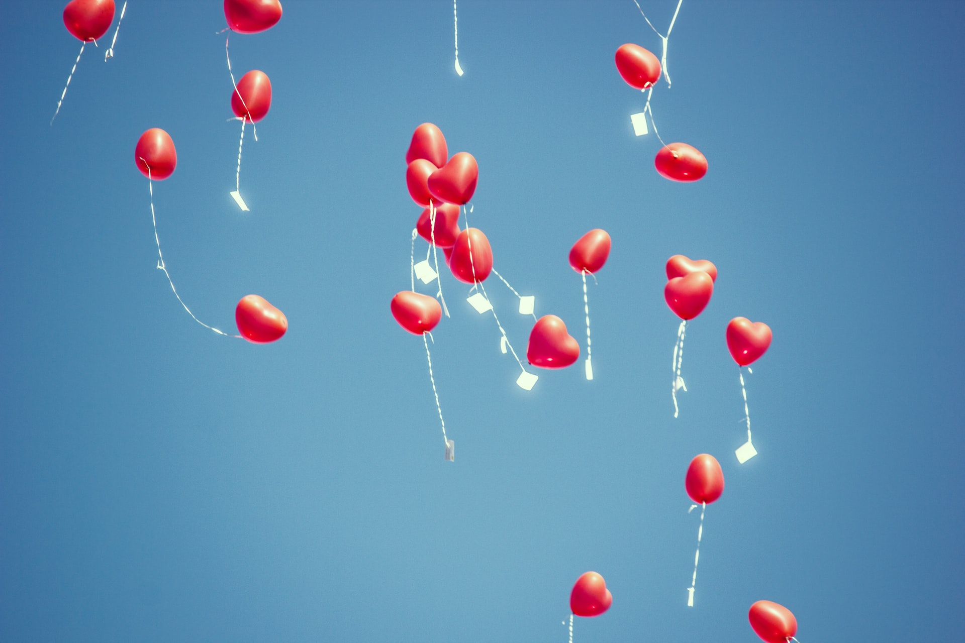 red heart balloons floating in the sky