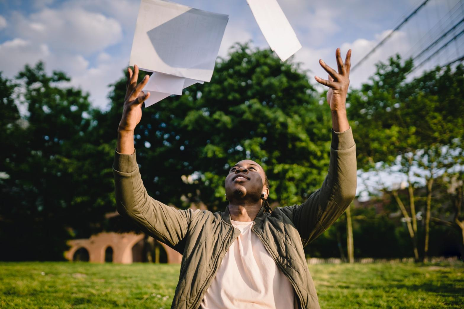 man throwing up papers in joy on an empty plot of land